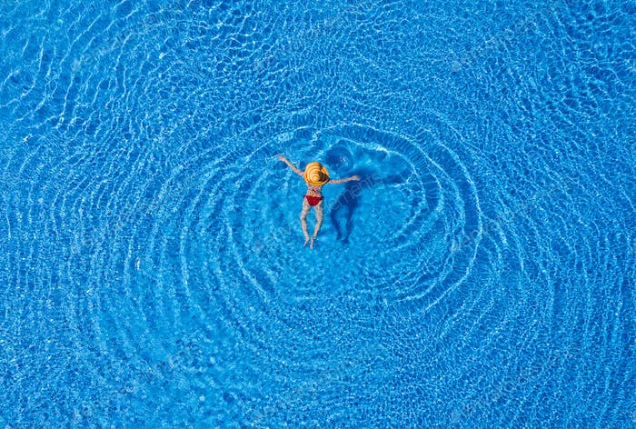 View from the top as a woman in a red swimsuit and a big yellow hat swims in the pool