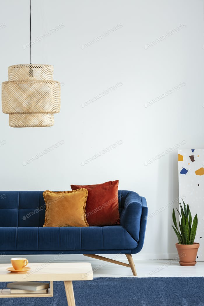 Retro lampshade above a simple, wooden coffee table on a navy bl