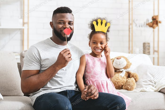 Positive black father and daughter holding selfie accessories