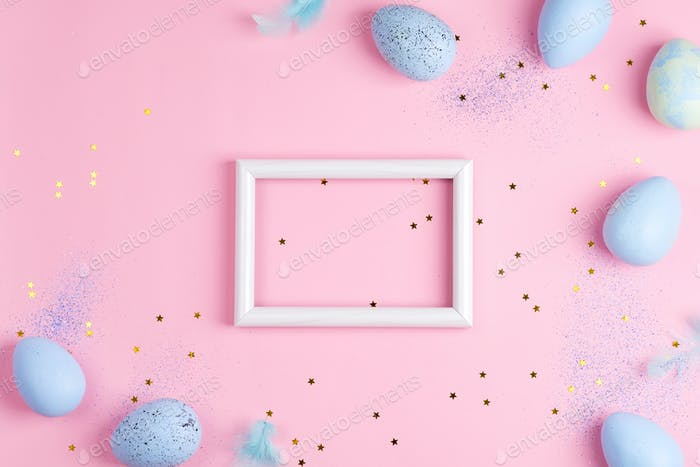 Corner frame from handmade painted eggs of pastel blue colors, photo frame and light feathers on a