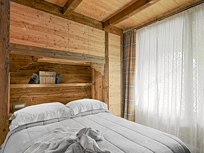 Interiors of a Rustic Bedroom with Wooden Wainscoting and Wooden Ceiling