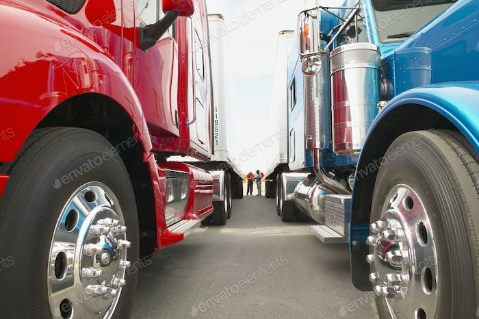 Lkw-Fahrer im Stehen zwischen Lastwagen der Klasse 8 und Anhänger auf einem Parkplatz.