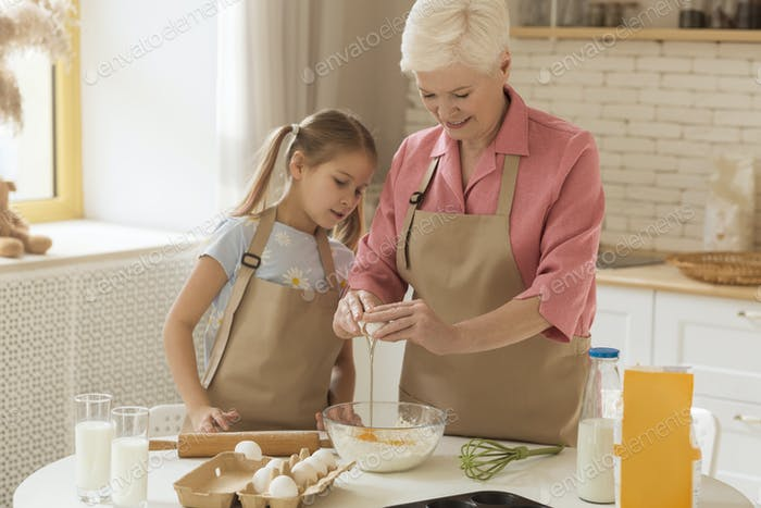 Baking together. Older lady and cute girl making dough together in kitchen