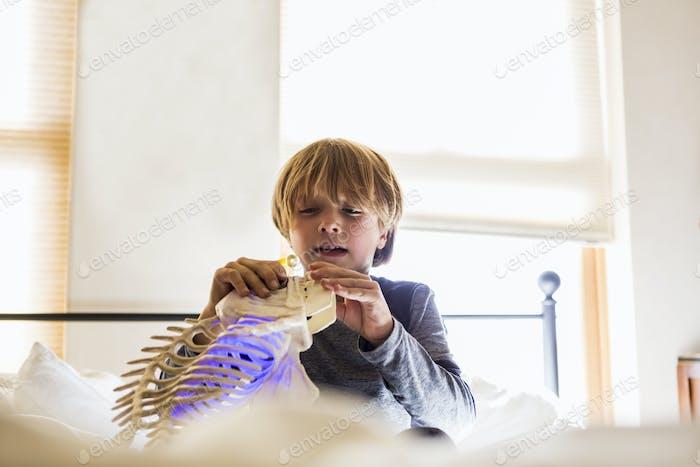 6-jähriger Junge spielt mit seinem Spielzeug auf seinem Bett