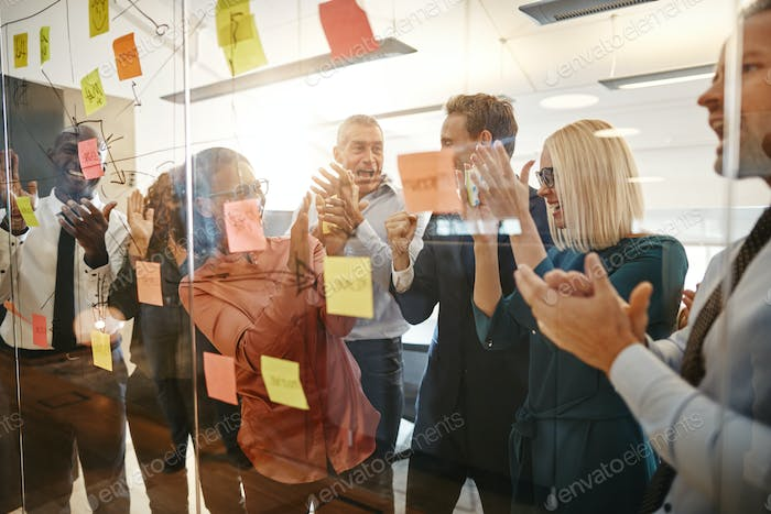 Laughing businesspeople clapping after an office brainstorming session