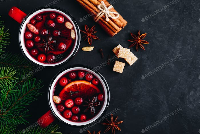 Mulled Wine Hot Drink with Cranberries, oranges, apples and spices on dark concrete background.