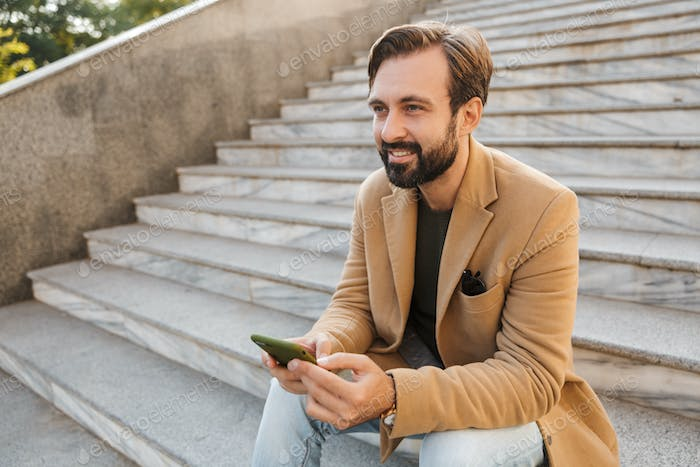 Image of handsome man holding smartphone while sitting on stairs outdoors