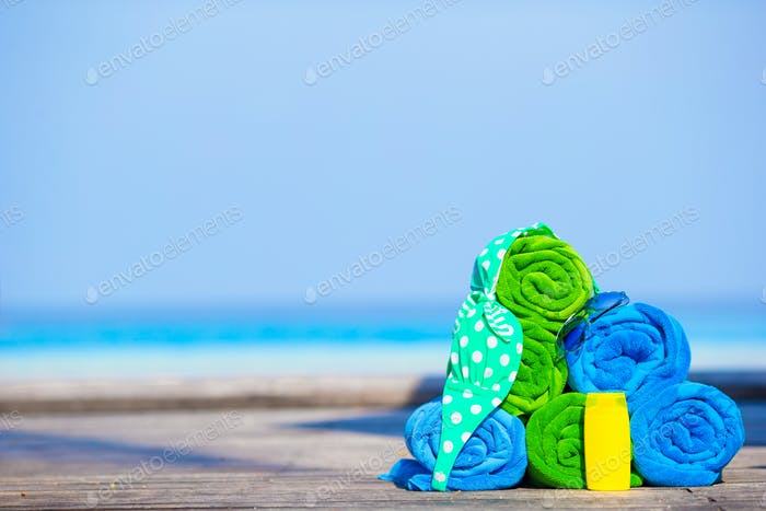 Beach and summer vacation accessories concept - close-up of colorful towels, swimming goggles and
