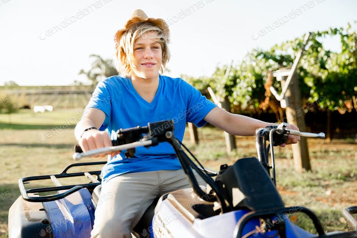 Boy riding farm truck in vineyard
