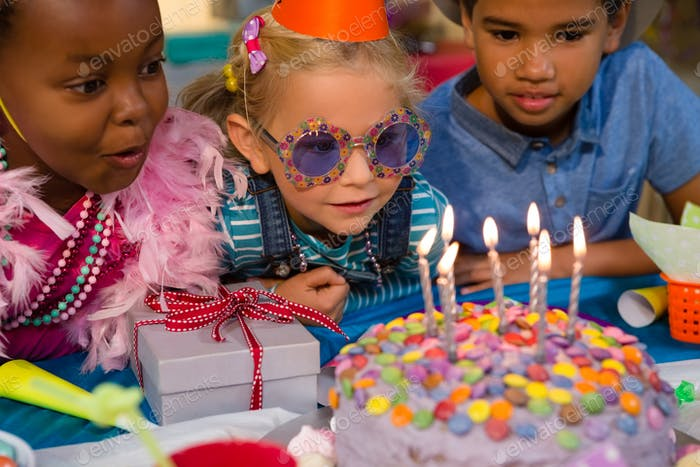 Close up of children looking at birthday cake