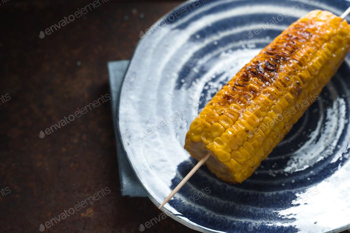 Roasted corn with salt on a blue plate on a metal table