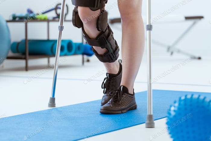 Injured patient in a leg brace exercising on a blue mat in a physiotherapy office