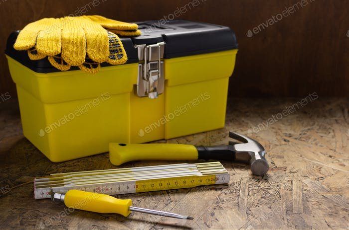Construction tools and toolbox on wooden tablel background texture. Tool box