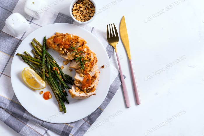 Grilled chicken breast with grilled asparagus and lemon slice on a napkin on stone background