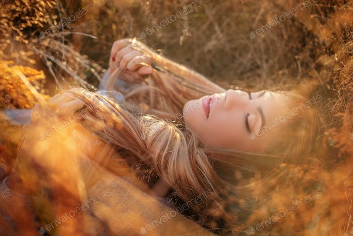 Blonde Frau in Sonnenbrille liegt in goldenem Gras.