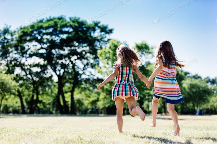Two happy friends holding hands and running in the park.