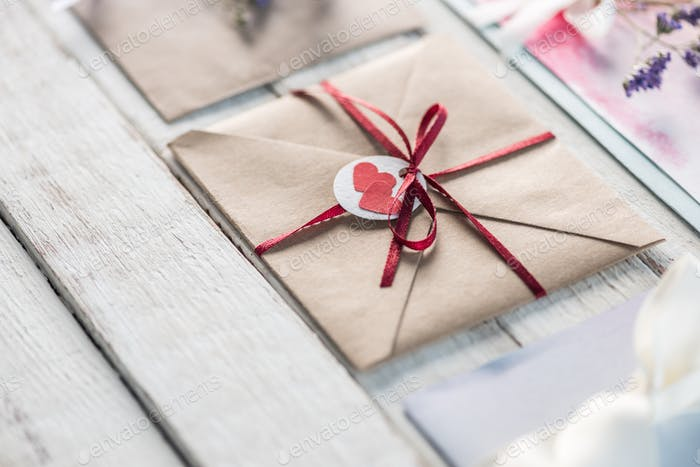 collection of envelopes or invitations on white wooden tabletop, wedding invitation card design