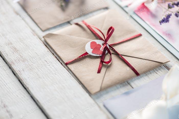Sammlung von Umschlägen oder Einladungen auf weißer Holzplatte, Hochzeits-Einladungskarte