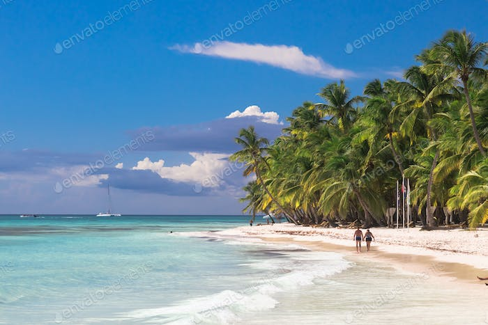 Couple walk on tropical island beach with perfect sunny sky