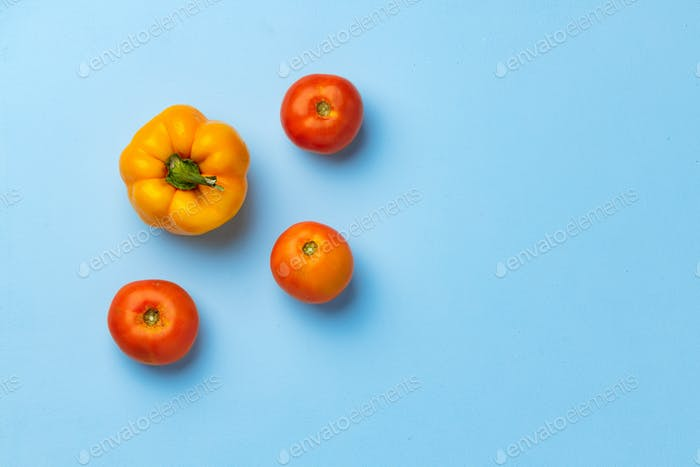 Three tomatoes and bell pepper on blue background