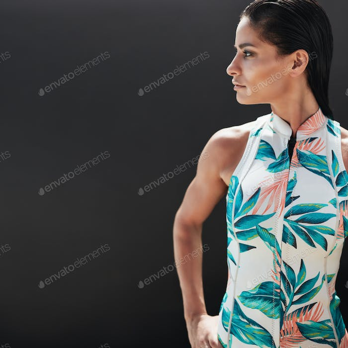 Beautiful young woman standing against black background