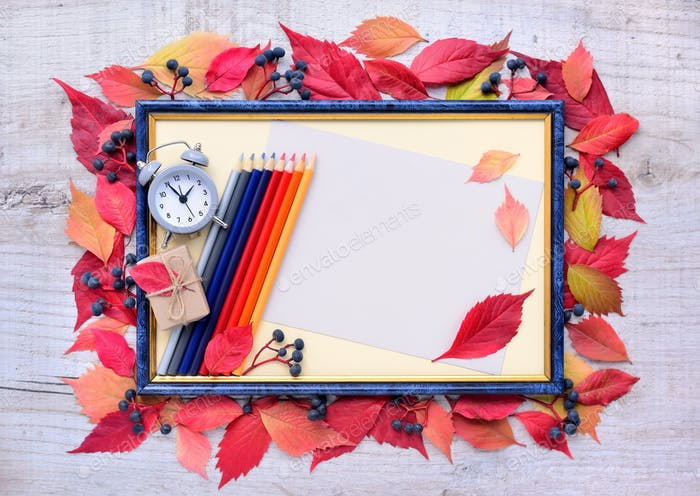 Autumn leaves composition with picture frame, alarm clock, penci