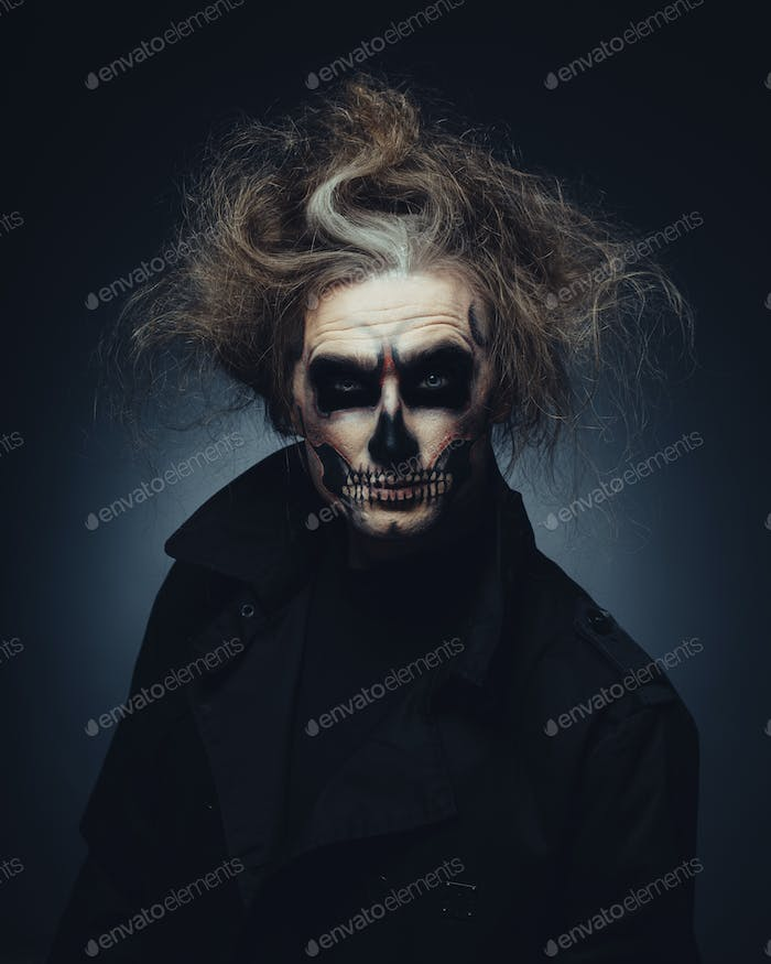 Skull makeup portrait of young man. Halloween face art.