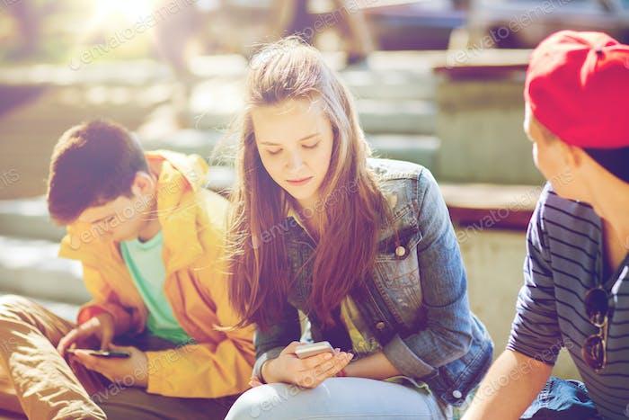 teenage friends with smartphones outdoors