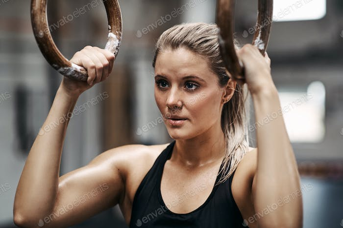 Fit young woman exercising with rings at a gym