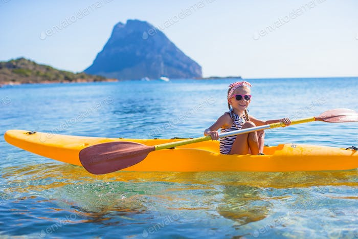 Little brave cute girl kayaking in the clear blue sea