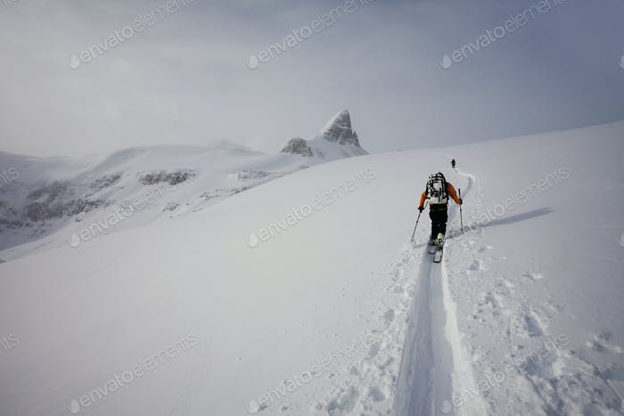 Two skiers ascending a ridge in mist and cloud conditions in snow in the mountains