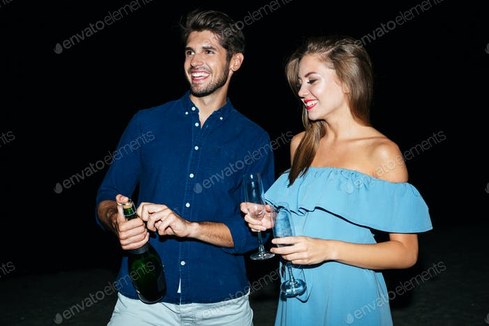 Couple opening bottle of champagne on the beach at night