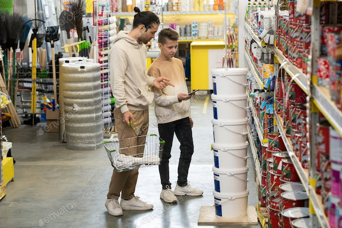 Father and son standing by one of displays in hardware store