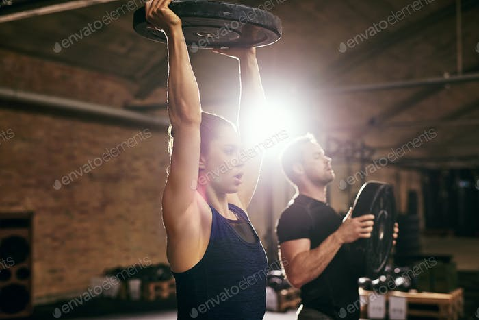Strong young woman holding heavy barbell up