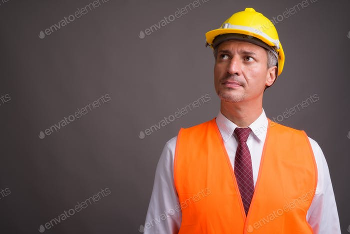 Portrait of man construction worker against gray background