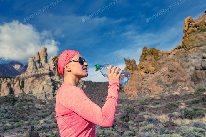 Woman trail runner drinking in inspiring mountains