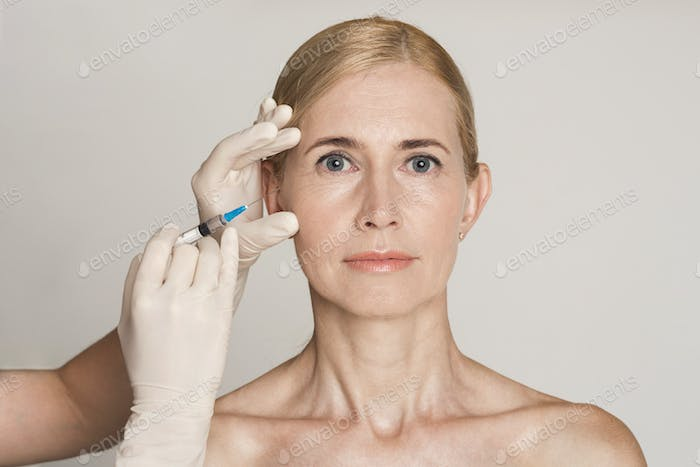 Plastic Surgery. Middle Aged Woman Receiving Botox Injection