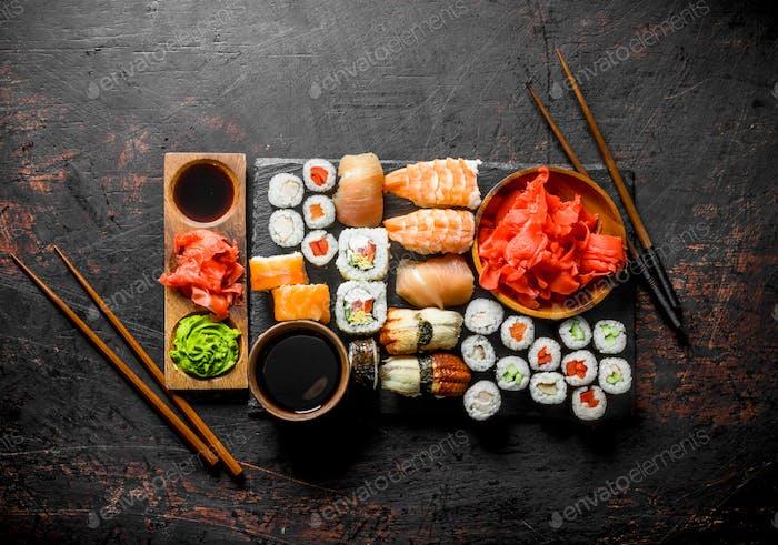 Verschiedene Brötchen, Sushi und Maki auf einem Stone Board mit Sojasauce und Ingwer.