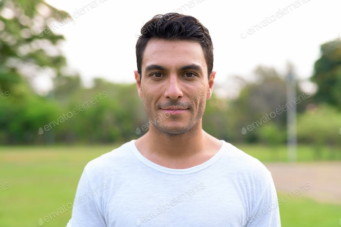 Face of young handsome Hispanic man at the park