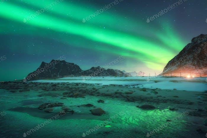 Aurora borealis über den verschneiten Bergen und Sandstrand