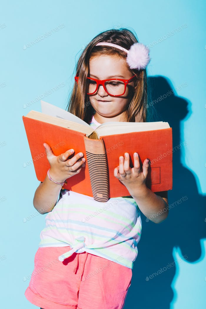 Little girl reading a book, wearing funny red glasses.