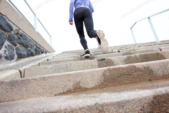 Female runner on wet staircase outside