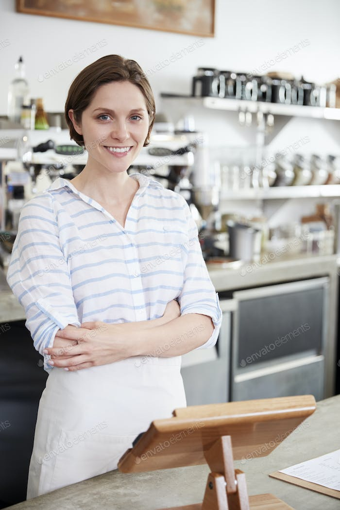Young smiling woman behind counter at coffee shop, vertical