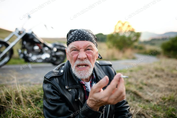 Angry senior man traveller with motorbike in countryside, smoking.