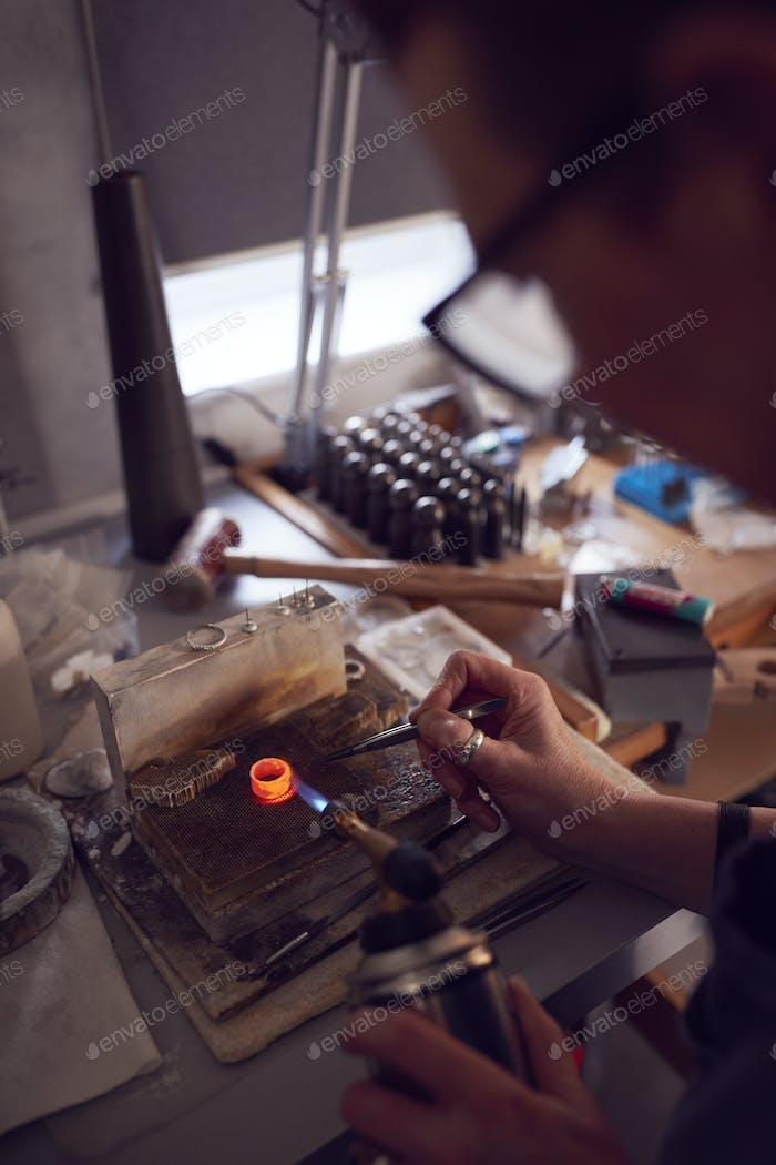 Close Up Of Male Jeweller Working On Ring With Blowtorch In Studio