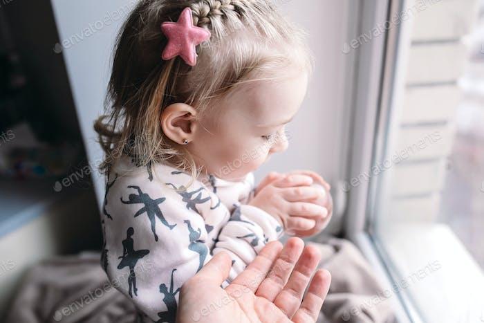 Little girl sitting near the window