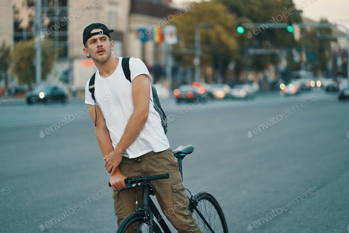 Man riding bicycle in urban city holding hands on handlebar