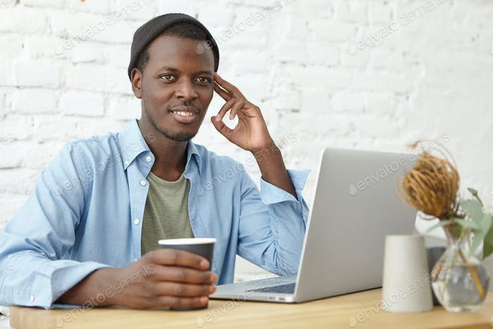 Modern urban lifestyle and technologies concept. Attractive young African American male freelancer w