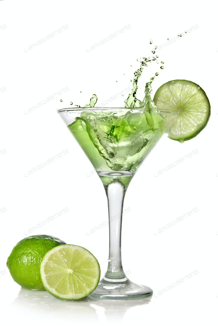 Green alchohol cocktail with splash and green lime isolated on w
