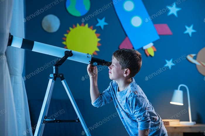Boy stargazing at night with telescope